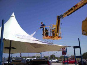 personal de limpieza desinfectando y limpiando techo de lona