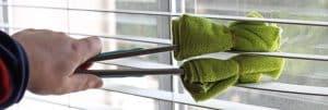 personal de limpieza desinfectando y limpiando persianas